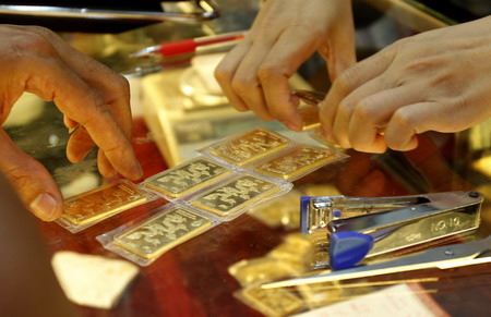 Gold bars are counted before given to a customer at a gold shop in Hanoi